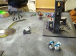 The Ork Dreadnought closes in on the Tau Stealth suits in the ruins